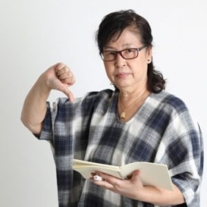 Unhappy woman giving a thumbs down and holding a book