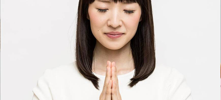 A close-up photo of Marie Kondo with eyes closed, head slightly bowed, and palms clasped together