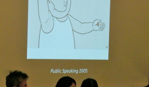 """4 speakers in front of a projector screen displaying """"Public Speaking 2005"""""""