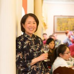 Woman smiling for the camera holding a wine glass, black bamboo blouse